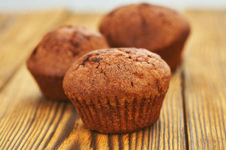Photo for Chocolate muffin with dark background test on an old wooden table. - Royalty Free Image