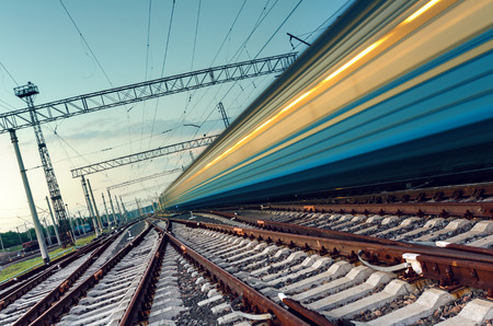 Foto de High speed passenger train on tracks with motion blur effect at sunset. Railway station in Ukraine - Imagen libre de derechos