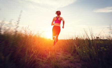 Foto de Young woman running on a rural road at sunset in summer field. Lifestyle sports background - Imagen libre de derechos