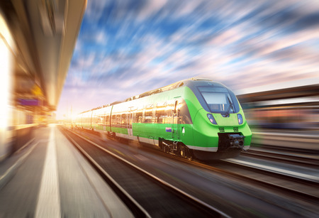 Foto de High speed train in motion at the railway station at sunset in Europe. Beautiful green modern train on the railway platform with motion blur effect. Industrial scene with passenger train on railroad - Imagen libre de derechos