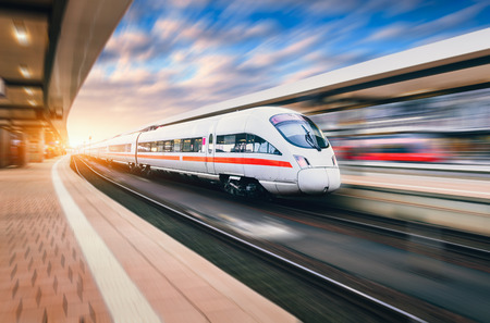 Foto per White modern high speed train in motion on railway station at sunset. Train on railroad track with motion blur effect in Europe in evening. Railway platform. Industrial landscape. Railway tourism - Immagine Royalty Free