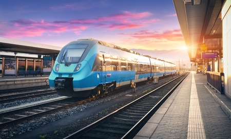 Photo for Modern high speed commuter train on the railway station and colorful sky with clouds at sunset in Europe. Industrial landscape with blue passenger train on railway platform. Railroad background - Royalty Free Image