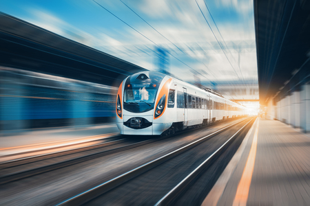 Foto per High speed train at the railway station at sunset in Europe. Modern intercity train on railway platform. Urban scene with beautiful passenger train on railroad and buildings. Railway landscape - Immagine Royalty Free