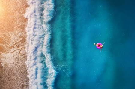 Photo for Aerial view of young woman swimming on the pink swim ring in the transparent turquoise sea in Oludeniz. Summer seascape with girl, beach, beautiful waves, blue water at sunset. Top view from drone - Royalty Free Image