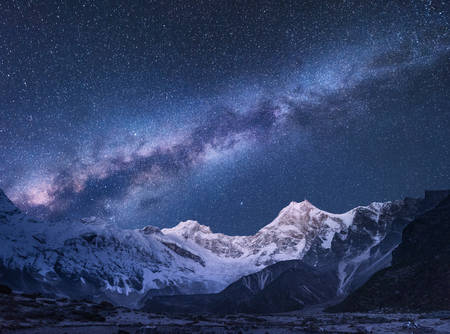 Foto de Milky Way and mountains. Amazing scene with himalayan mountains and starry sky at night in Nepal. Rocks with snowy peak and sky with stars. Beautiful Himalayas. Night landscape with bright milky way - Imagen libre de derechos
