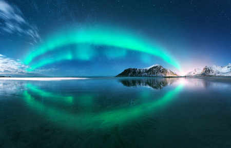 Photo pour Aurora. Northern lights in Lofoten islands, Norway. Starry blue sky with polar lights. Night winter landscape with aurora, sea with sky reflection, beach, mountains, city lights. Green aurora borealis - image libre de droit