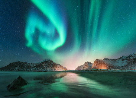 Foto de Aurora borealis in Lofoten islands, Norway. Aurora. Green northern lights. Starry sky with polar lights. Night winter landscape with aurora, sea with sky reflection, stones, beach and snowy mountains - Imagen libre de derechos