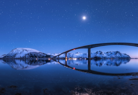 Foto de Amazing bridge and starry sky with beautiful reflection in water. Night landscape with bridge, snowy mountains, blue sky with moon and bright stars reflected in sea. Winter in Lofoten islands, Norway  - Imagen libre de derechos