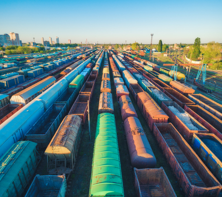 Photo pour Aerial view of colorful freight trains. Cargo wagons on railway station. Wagons with goods on railroad. Heavy industry. Industrial landscape with train, railway platfform at sunset. Top view. Depot - image libre de droit