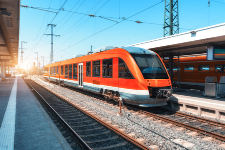 Foto per High speed red train on the railway station at sunset in summer. Modern commuter train on the railway platform. Industrial scene with railroad. Passenger transportation. intercity vehicle. Travel - Immagine Royalty Free