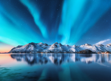 Photo pour Northern lights and snow covered mountains in Lofoten islands, Norway. Aurora borealis. Starry sky with polar lights and snowy rocks reflected in water. Night winter landscape with aurora, sea. Nature - image libre de droit