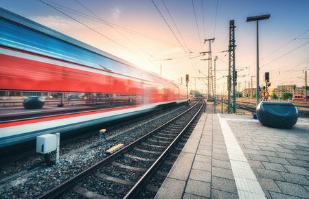 Foto per Red high speed train in motion on the railway station at colorful sunset. Blurred modern intercity train with sky reflection in windows on the railway platform. Passenger transportation. Railroad - Immagine Royalty Free