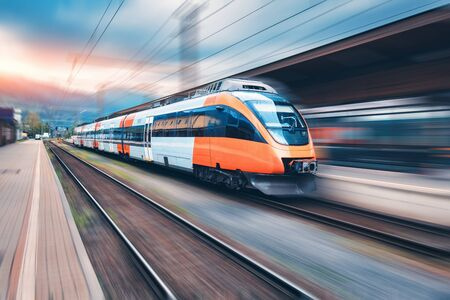 Photo pour High speed orange train in motion on the railway station at sunset. Modern intercity passenger train with motion blur effect on the railway platform. Industrial. Railroad in Europe. Transport - image libre de droit