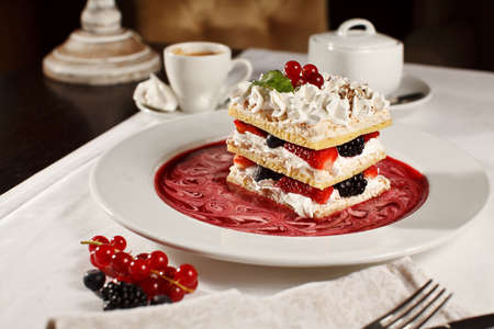 Appetizing french millefeuilles raspberry, blackberry, strawberry dessert with coffee