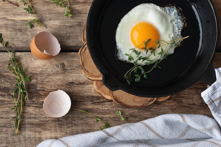 Photo pour Scrambled eggs in an iron pan on the rustic wooden table - image libre de droit