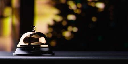 Foto de Golden reception bell on black table with shallow depth of field black background. Service concept - Imagen libre de derechos