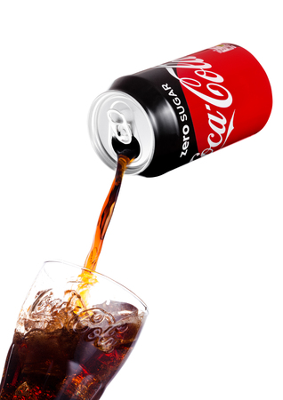 Foto de LONDON, UK - JANUARY 02, 2018: Pouring Coca Cola Zero soda drink from aluminium tin to glass on white background. The drink is produced and manufactured by The Coca-Cola Company. - Imagen libre de derechos
