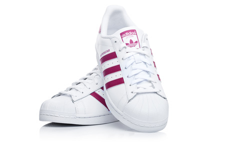 Photo pour LONDON, UK - JANUARY 12, 2018: Adidas Originals Superstar red shoes on white background.German multinational corporation that designs and manufactures sports shoes, clothing and accessories. - image libre de droit