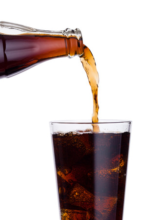 Foto de Pouring cola soda drink from bottle to glass  with ice cubes on white background - Imagen libre de derechos