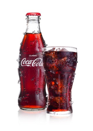 Foto de LONDON, UK - FEBRUARY 02, 2018: Cold bottle and glass of Classic Coca Cola  drink on white background with ice and dew. The drink is produced and manufactured by The Coca-Cola Company. - Imagen libre de derechos