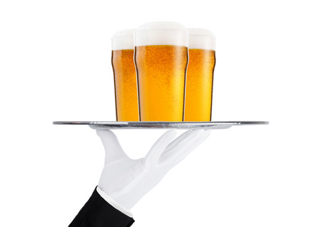 Foto de Hand with glove holds tray with lager beer glasses with foam and dew isolated on white background - Imagen libre de derechos