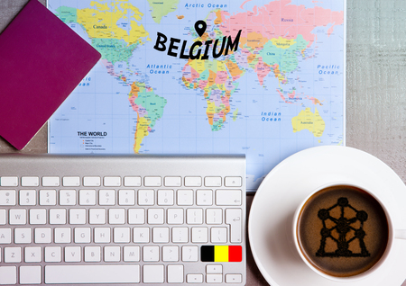 Foto de Travel holiday concept with coffee and map with flag on keyboard and passport on wooden table. Travel to Belgium Brussels - Imagen libre de derechos