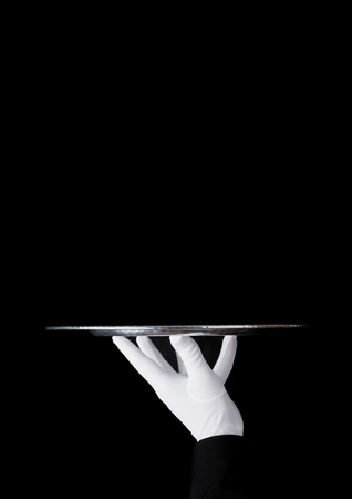 Photo pour Servant wearing white glove holds stainless steel tray on black background - image libre de droit