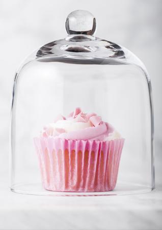 Foto de Cupcake muffin with raspberry cream dessert on marble background with pink candies - Imagen libre de derechos