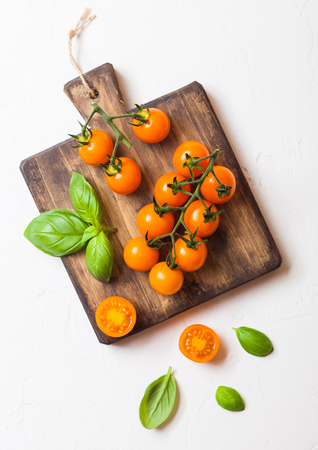 Photo for Organic Cherry Orange Rapture Tomatoes on the Vine with basil on chopping board on white background. - Royalty Free Image