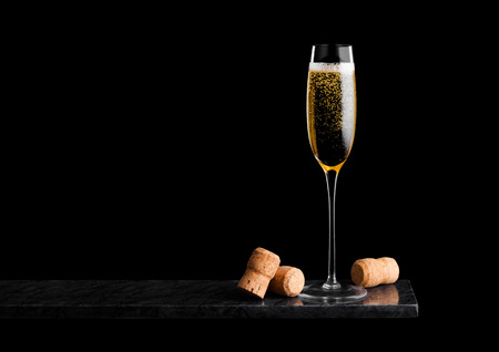 Photo for Elegant glass of yellow champagne with corks on black marble board on black. - Royalty Free Image