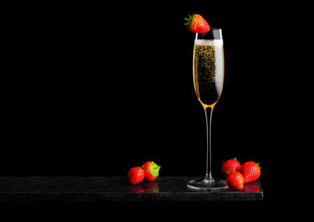 Photo for Elegant glass of yellow champagne with strawberry on top and fresh berries on black marble board on black. - Royalty Free Image