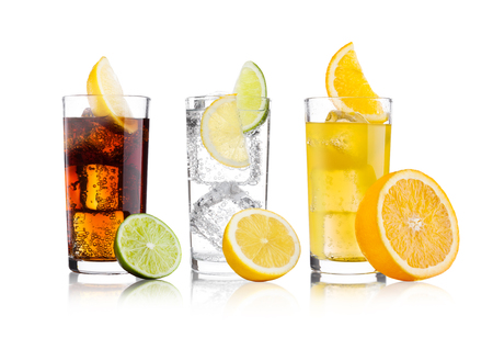 Foto de Glasses of cola and orange soda drink and lemonade sparkling water on white background with ice cubes lemons and lime bits - Imagen libre de derechos