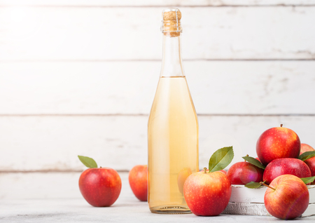 Foto per Bottle of homemade organic apple cider with fresh apples in box on wooden background, Glass with ice cubes - Immagine Royalty Free