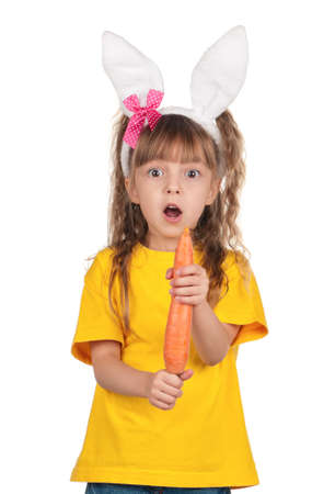 Portrait of surprised little girl with bunny ears with carrot over white background