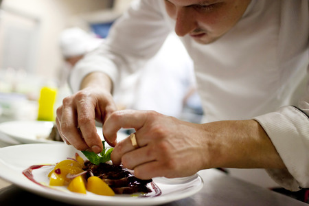 Foto de Chef is decorating delicious dish, motion blur on hands - Imagen libre de derechos