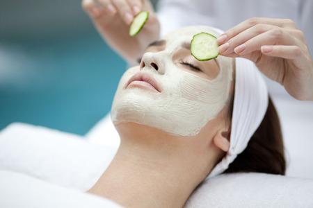 Foto de Beautiful young woman receiving facial mask of cucumber in beauty - Imagen libre de derechos