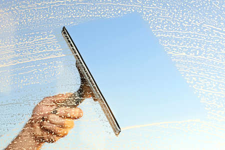 Photo pour A hand and a squeegee cleaning windows - image libre de droit