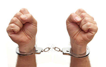 Foto de Closeup of a person breaking the chains on metal handcuffs - Imagen libre de derechos