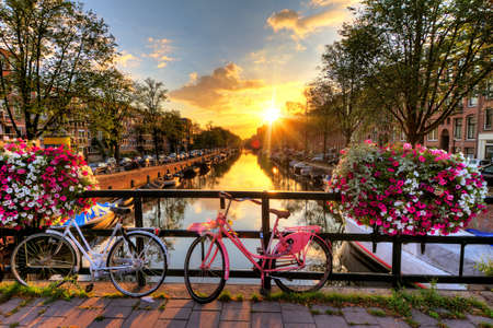 Photo pour Beautiful sunrise over Amsterdam, The Netherlands, with flowers and bicycles on the bridge in spring - image libre de droit