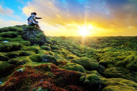 Foto de Romantic couple watches the sunrise over the beautiful volcanic landscape of Eldhraun in Iceland - Imagen libre de derechos