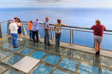 Foto de Tourists looking at the view at the Cabo Girao platform, a viewpoint on top of the big cliffs of the island Madeira, on October 11, 2015 - Imagen libre de derechos