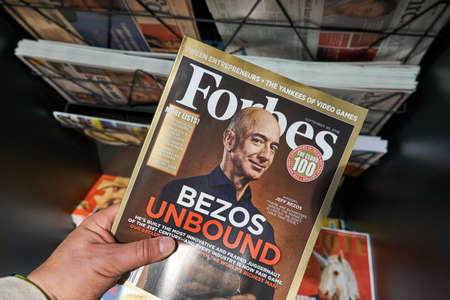 Foto de AMSTERDAM, NETHERLANDS - OCTOBER 08, 2018: Forbes magazine with Jeff Bezos on the cover in a hand. Jeff Bezos is president of Amazon. Forbes is an American family-controlled business magazine. - Imagen libre de derechos