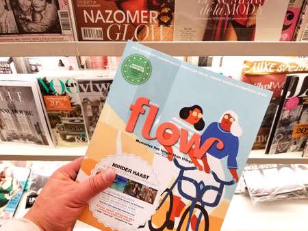 Foto de AMSTERDAM, NETHERLANDS: - OCTOBER 8, 2018: Flow magazine in a hand over a stack of magazines. - Imagen libre de derechos