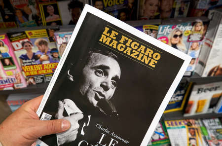Foto de MONTREAL, CANADA - OCTOBER 9, 2018: Le Figaro magazine in a hand with Charles Aznavour on the front cover over a stack of magazines. Le Figaro magazine is a French language weekly news magazine - Imagen libre de derechos