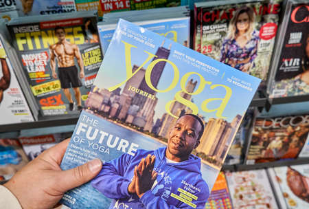 Foto de MONTREAL, CANADA - OCTOBER 9, 2018: Yoga Journal with Marshawn Feltus in a hand over a stack of magazines. Yoga Journal is an American media company that publishes a magazine, makes dvds etc. - Imagen libre de derechos