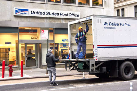 Foto de NEW YORK, USA - DECEMBER 14, 2018: USPS postman on a mail delivery truck in New York. USPS is an independent agenc of US federal government responsible for providing postal service in the US. - Imagen libre de derechos