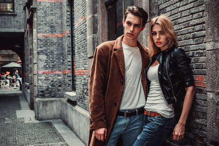Photo pour Young and trendy man and woman posing of the street with brick walls. Fashion style - image libre de droit