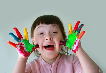 Foto de Cute little girl with painted hands. Isolated on grey background. - Imagen libre de derechos