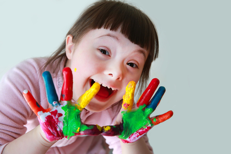 Foto de Cute little girl with painted hands. Isolated on grey background. - Imagen libre de derechos