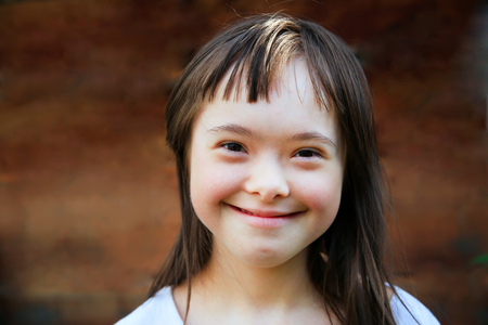 Photo for Cute smiling down syndrome girl on the brown background - Royalty Free Image